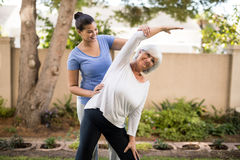 Smiling trainer assisting senior woman with hand raised Stock Images