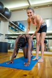 Smiling trainer assisting a woman while practicing pilates Stock Photos