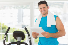 Smiling trainer with clipboard in gym. Portrait of a smiling trainer with clipboard standing in the gym Royalty Free Stock Photo