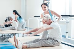 Smiling trainer helping crippled man train his muscles. Trying harder. Determined old grey-haired men sitting on bed and having painful facial expression while a Royalty Free Stock Image