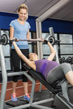 Smiling trainer helping pregnant woman lifting barbell Stock Photo