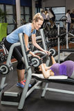 Smiling trainer helping pregnant woman lifting barbell Stock Photos