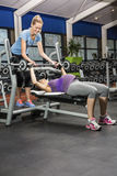 Smiling trainer helping pregnant woman lifting barbell Royalty Free Stock Image