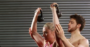 Smiling trainer helping woman lifting kettlebells. At the gym stock video footage
