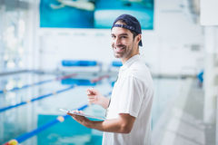 Smiling trainer holding clipboard Stock Photo