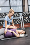 Smiling trainer manipulating pregnant woman. Smiling trainer manipulating pregnant women at the gym Stock Image