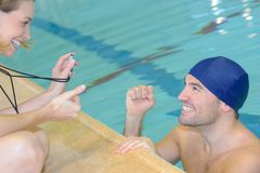 Smiling trainer showing stopwatch at swimmer at leisure center Royalty Free Stock Photo