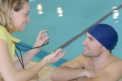 Smiling trainer showing stopwatch at swimmer at leisure center Stock Image