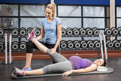 Smiling trainer stretching pregnant womans leg Royalty Free Stock Image