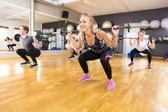 Smiling training group doing squat exercises at fitness gym Royalty Free Stock Images