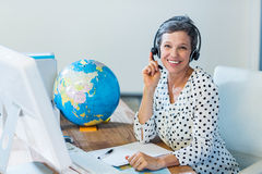 Smiling travel agent sitting at her desk Stock Photography
