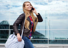Smiling travel girl with bag talking on mobile phone Stock Image