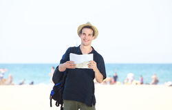 Smiling travel man standing by the beach with map Stock Photo