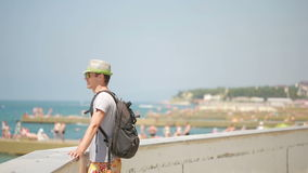 Smiling travel man standing by the beach. tourist with a backpack on the sea. stock video