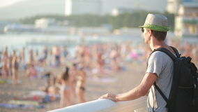 Smiling travel man standing by the beach. tourist with a backpack on the sea. stock footage