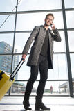 Smiling travel man walking with cell phone and bag Royalty Free Stock Photography