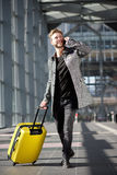 Smiling travel man walking with cell phone and suitcase Royalty Free Stock Photo