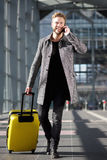 Smiling travel man walking with mobile phone and suitcase Royalty Free Stock Photo