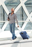 Smiling travel man walking with suitcase and smart phone Stock Photography