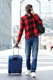 Smiling travel man walking with suitcase and talking on mobile phone Stock Photo