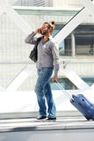 Smiling travel man walking and talking on cellphone Stock Photography