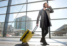 Smiling travel man walking and talking on mobile phone Royalty Free Stock Images