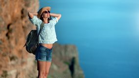 Smiling travel tanned woman relaxing rising hand standing on mountain over sea feeling positive emotion. Beautiful backpacker young hiker female enjoying stock video