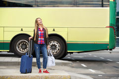 Smiling travel woman standing at bus terminal with bags Royalty Free Stock Photos