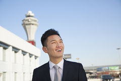 Smiling Traveler looking at sky at airport Royalty Free Stock Images