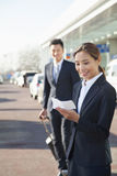 Smiling Traveler looking at ticket at airport arrivals area Royalty Free Stock Photography