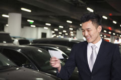 Smiling Traveler looking at ticket in airport parking lot Stock Images