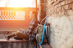 Smiling traveler man sitting on the edge of the roof and listening music in earphones with backpack and skateboard. Brave smiling traveler man sitting on the Royalty Free Stock Photography