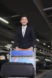 Smiling Traveler pushing cart in airport parking lot Stock Image