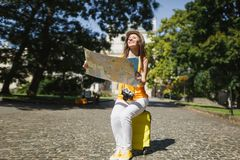 Smiling traveler tourist woman in casual clothes, hat sitting on suitcase holding city map search route in city outdoor. Girl traveling abroad to travel on stock image