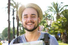 Smiling traveling man standing outside with hat and bag Royalty Free Stock Images
