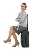 Smiling traveling woman sitting on suitcase Royalty Free Stock Images