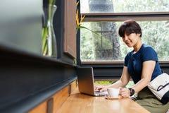 Smiling traveller woman checking booking travel plan on laptop w royalty free stock photos