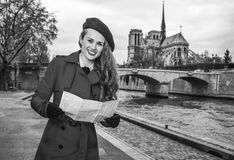 Smiling traveller woman on embankment in Paris, France with map Royalty Free Stock Images
