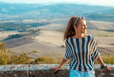 Smiling traveller woman in Tuscany looking into distance. Smiling elegant traveller woman in striped blouse in Tuscany looking into the distance royalty free stock image