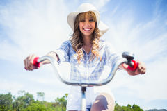 Smiling trendy blonde riding her bike Royalty Free Stock Images