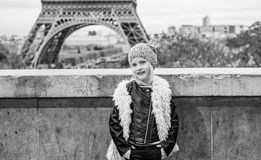Smiling trendy child in front of Eiffel tower in Paris, France. Bold Winter in Paris. Full length portrait of smiling trendy child in the front of Eiffel tower Royalty Free Stock Images