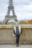 Smiling trendy child in front of Eiffel tower in Paris, France. Bold Winter in Paris. Full length portrait of smiling trendy child in the front of Eiffel tower Royalty Free Stock Photography