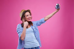 Smiling trendy girl is taking selfie against pink background Stock Image