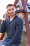 Smiling trendy guy talking on the phone outdoor. Stock Photo