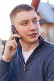 Smiling trendy guy talking on the phone outdoor. Royalty Free Stock Photo