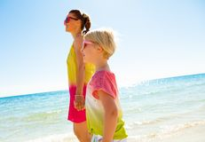 Smiling trendy mother and child on beach walking. Colorful and wonderfully cheerful mood. smiling trendy mother and child in colorful clothes on the beach Royalty Free Stock Photography