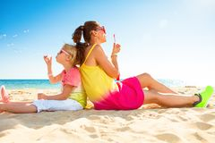 Smiling trendy mother and child on seashore blowing bubbles. Colorful and wonderfully cheerful mood. smiling trendy mother and child in colorful clothes on the Royalty Free Stock Photo