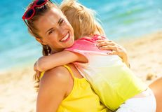 Smiling trendy mother and child on seashore hugging. Colorful and wonderfully cheerful mood. smiling trendy mother and child in colorful clothes on the seashore Stock Image