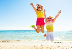 Smiling trendy mother and child on seashore jumping. Colorful and wonderfully cheerful mood. Full length portrait of smiling trendy mother and child in colorful Stock Images
