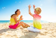 Smiling trendy mother and daughter on seacoast blowing bubbles. Colorful and wonderfully cheerful mood. smiling trendy mother and daughter in colorful clothes on royalty free stock image